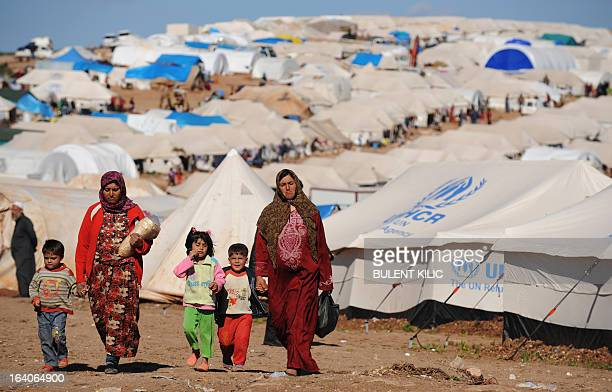 Syrian internally displaced people walk in the Atme camp, along the Turkish border in the northwestern Syrian province of Idlib, on March 19, 2013....