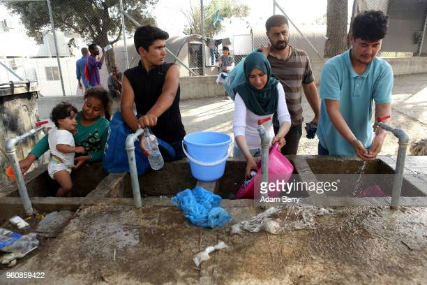 Syrian Iraqi and Afghan refugees collect water and wash clothing at the Moria refugee camp on May 20 2018 in Mytilene Greece Despite being built to...