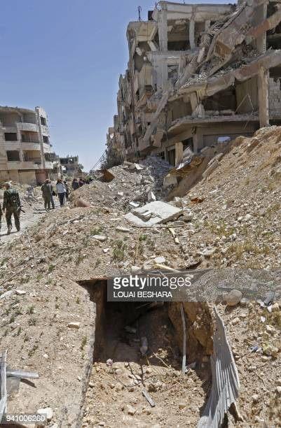 Syrian journalists and regime members are seen walking around a tunnel previously used by rebel-fighter for smuggling goods and taking shelter, in...