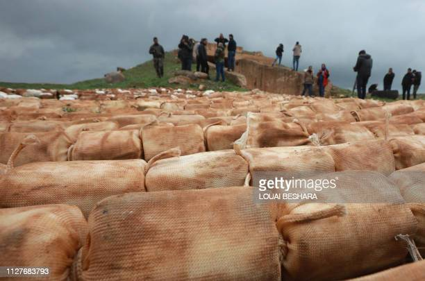 TOPSHOT Syrian journalists check what the Syrian army says are packs of C4 explosives that were found in the southern province of Daraa on February...