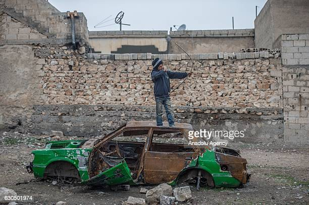 Syrian kid aims with his arrow over a wreckage of a car as Syrians live freely against all odds in Jarabulus after its cleansing of Daesh militants...