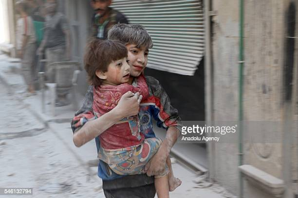 Syrian kid carries his brother after Russian air forces carried out an airstrike at opposition controlled Salihiyyin district in Aleppo Syria on July...