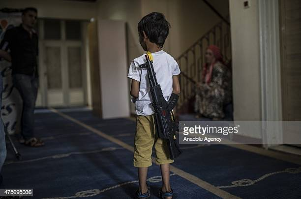Syrian kid carrying a toy rifle on his back is seen at a hotel in Gaziantep Turkey on June 02 2015 Some Syrian refugees who fled Syria due to the...