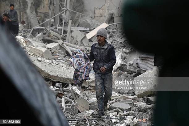 A Syrian kid collects items from the rubble of a destroyed building following air strikes on the Eastern Ghouta town of Douma a rebel stronghold east...
