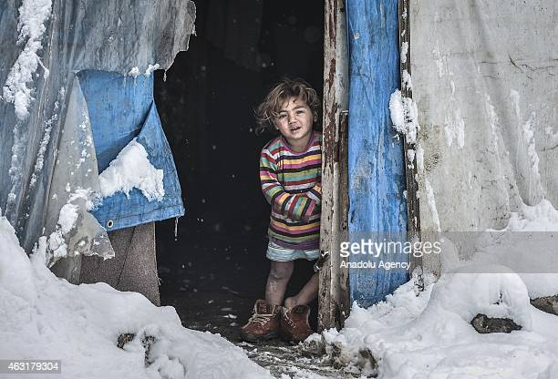 Syrian kid fled with her family from attacks of Islamic State of Iraq and Levant from Syria is seen in front of a hovel as they live in harsh...