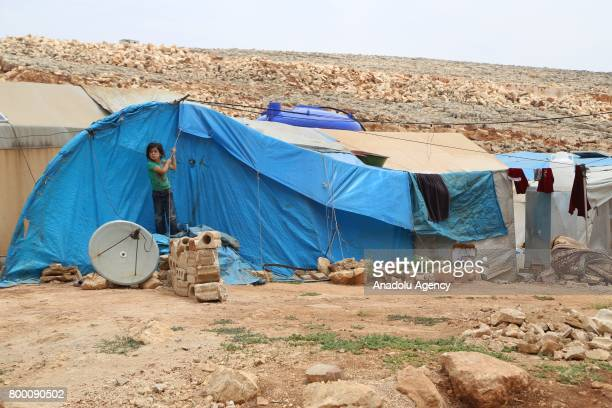 Syrian kid is seen in front of a tent during Muslim's holy month of Ramadan in Idlib Syria on June 23 2017 Ahead of Eid al Fitr Syrian people fled...