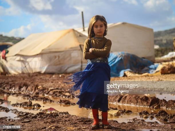 Syrian kid poses for a photo in mud after heavy rain caused flood damaging their camp in Idlib, Syria on January 15, 2021.