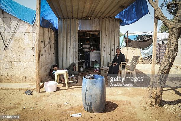 Syrian kid try to cool off in a bucket at Atmeh refugee camp in Idlib, Syria on May 19, 2015. More than 60 thousand refugees, fled their homes due to...