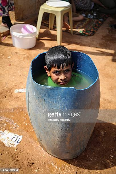 Syrian kid try to cool off in a bucket at Atmeh refugee camp in Idlib Syria on May 19 2015 More than 60 thousand refugees fled their homes due to the...