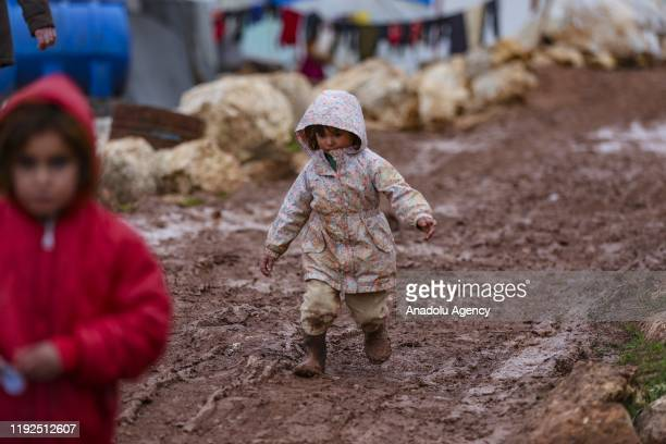 Syrian kid walks on muddy ground in Yavru Fida Camp with 90 tents in Idlib Syria on January 7 2020 Syrian families fled from Assad regime and Russian...