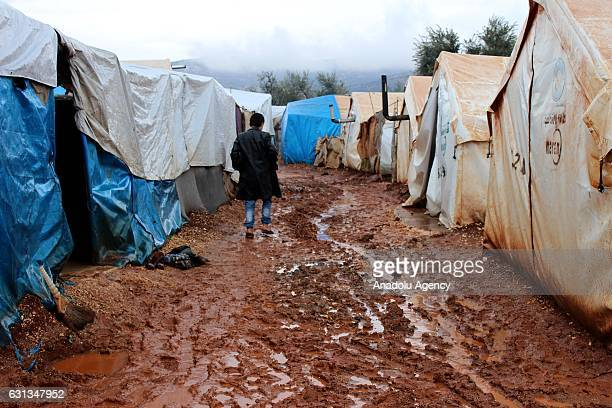 Syrian kid walks over a muddy road between tents at the Refugee camp as refugees live under winter conditions in Idlib Syria on January 9 2017