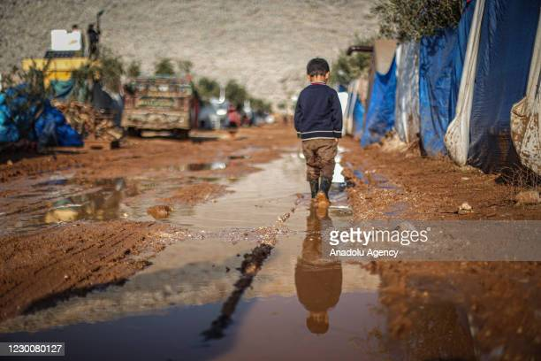 Syrian kid wearing plastic boots walks midst of muds in a tent camp which set up by war-weary Syrians with the help of arbitrary donations of NGOs...