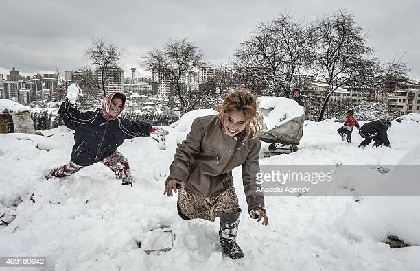 Syrian kids fled with their families from attacks of Islamic State of Iraq and Levant from Syria play with snow in front of a hovel as they live in...