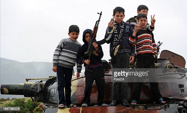 Syrian kids holding an assault rifle while standing on top of a tanker on April 16 in Darkoush Syria A team of 45 medical personnel arrived in Syria...