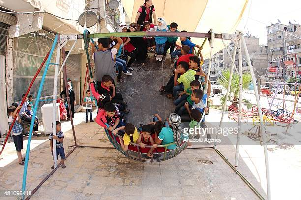 Syrian kids play at a playground which are brought for them during Eid alFitr in Aleppo Syria on July 17 2015 Eid alFitr is a religious holiday...