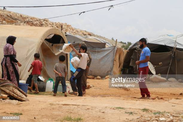 Syrian kids play in front of their tent during Muslim's holy month of Ramadan in Idlib Syria on June 23 2017 Ahead of Eid al Fitr Syrian people who...