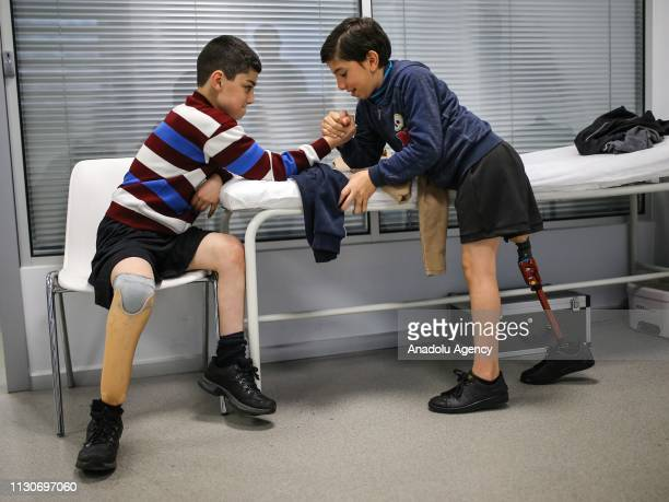 Syrian kids Taha and Ali who lost their legs during regime forces' assaults within civil war in Syria arm wrestle at Private Kuwait Istanbul Orthotic...
