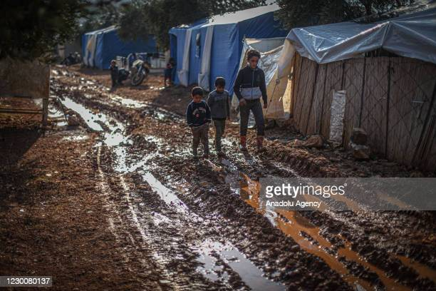 Syrian kids wearing plastic boots walk midst of muds in a tent camp which set up by war-weary Syrians with the help of arbitrary donations of NGOs...