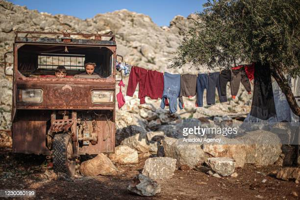Syrian kids wearing play in an old motorcycle midst of muds in a tent camp which set up by war-weary Syrians with the help of arbitrary donations of...
