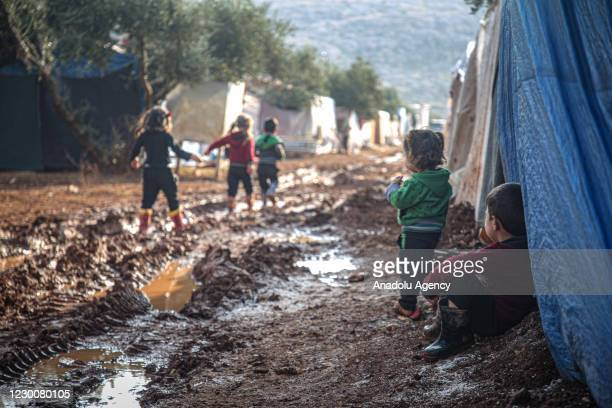 Syrian kids wearing slippers or plastic boots play midst of muds in a tent camp which set up by war-weary Syrians with the help of arbitrary...