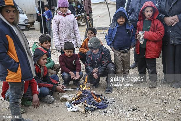 Syrian kids who fled bombing in Aleppo warm around the fire at a tent city close to the Bab alSalam border crossing on TurkishSyrian border near Azaz...