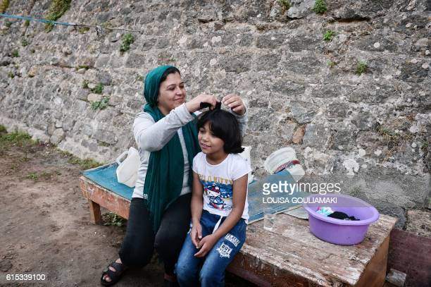 A Syrian Kurd mother combs Roza's hair as she prepares to go to a volunteerrun school in a refugee camp on the island of Chios on October 13 2016...