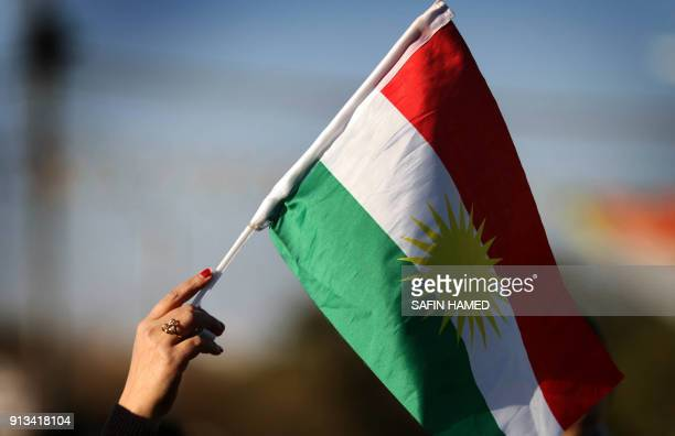 A Syrian Kurd waves the Kurdish flag in the northern Iraqi city of Arbil the capital of the autonomous Kurdistan region during a demonstration on...