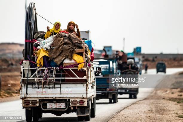 TOPSHOT Syrian Kurdish and Arab families are pictured fleeing in the countryside of the town of Darbasiyah on the border between Syria and Turkey...