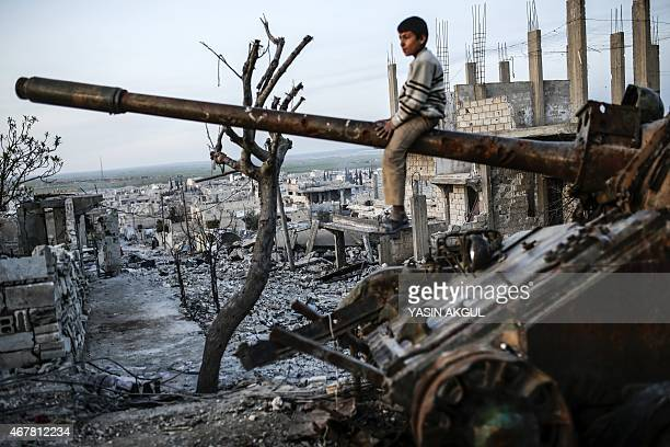 A Syrian Kurdish boy sits on a destroyed tank in the Syrian town of Kobane also known as Ain alArab on March 27 2015 Islamic State fighters were...