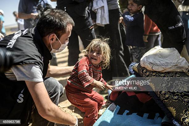 A Syrian Kurdish child cries as Turkish police search their bags after they crossed the border between Syria and Turkey at the southeastern town of...