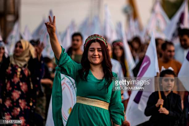 Syrian Kurdish demonstrator flashes the V for victory sign as she marches in the northeastern city of Qamishli on August 27, 2019 during a protest...