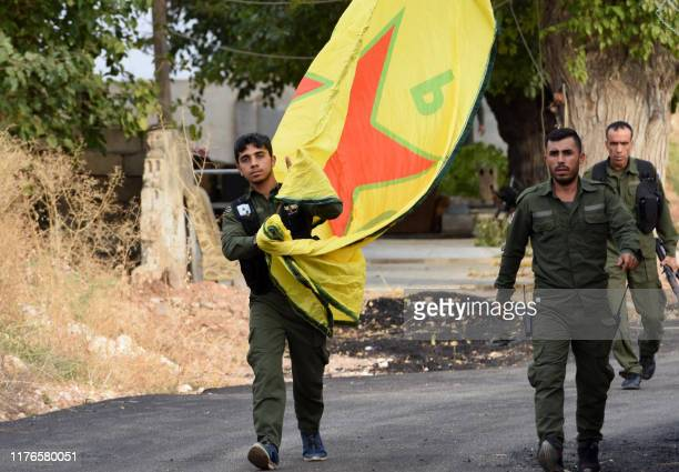 Syrian Kurdish fighters walk carrying a People's Protection Units yellow flag in the Syrian Kurdish town of Kobane also known as Ain alArab along the...