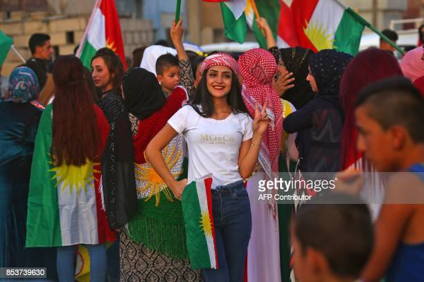 A Syrian Kurdish girl flashes the victory gesture as she poses for a picture while celebrating in the northeastern Syrian city of Qamishli on...
