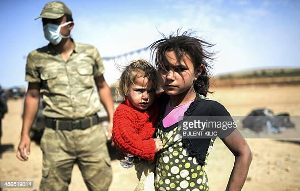 A Syrian Kurdish girl holds her sister in the southeastern town of Suruc in the Sanliurfa province after they crossed the border between Syria and...