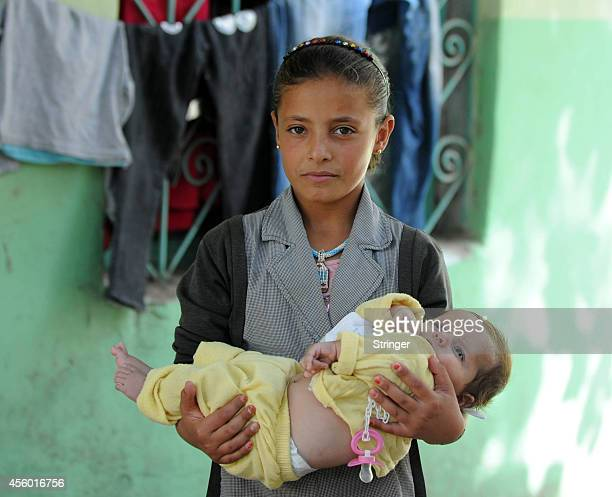 A Syrian Kurdish girl holds his sister in a school serving as a temporary shelter for refugees in southeastern town of Suruc Sanliurfa province of...