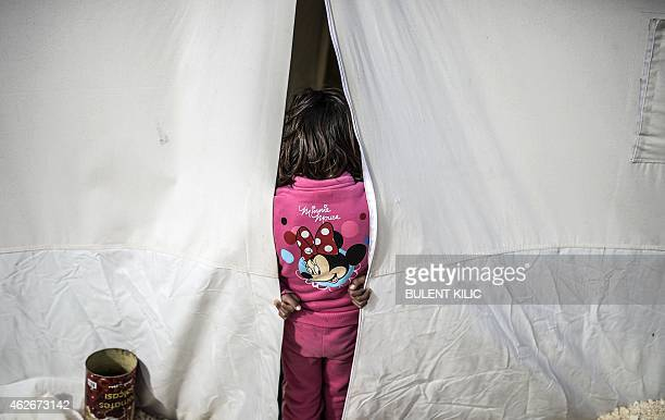 Syrian Kurdish girl stands at the entrance of a tent in an UNHCR refugee camp on February 2 at Suruc, in Sanliurfa. AFP PHOTO/BULENT KILIC