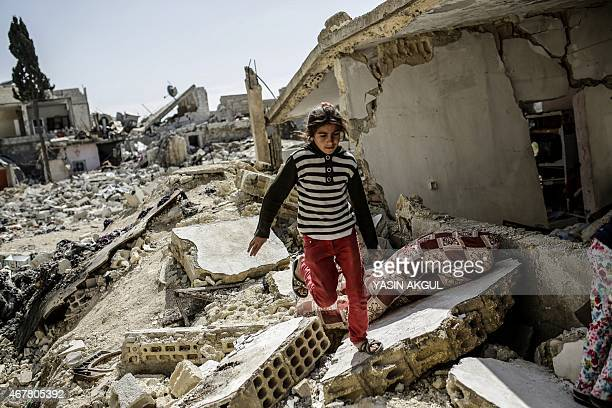 A Syrian Kurdish girls walks through the rubble of a house in the Syrian town of Kobane also known as Ain alArab on March 27 2015 Islamic State...