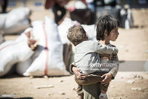 Syrian Kurdish kids look around as a group of Syrian Kurds fled from the clashes between Islamic State of Iraq and the Levant and Syrian Kurdish...