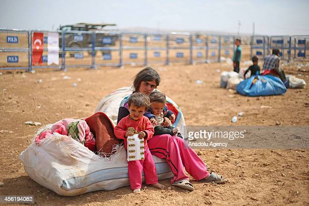 Syrian Kurdish kids sitting on their belongings look around as a group of Syrian Kurds fled from the clashes between Islamic State of Iraq and the...
