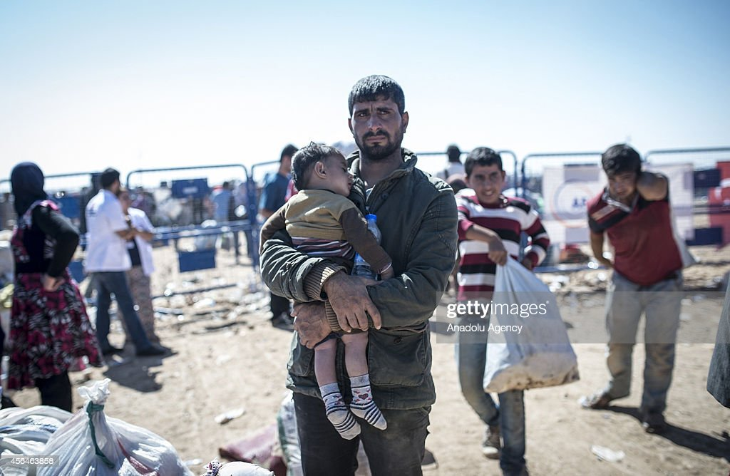 Syrian Kurdish man holding his kid, fled from the clashes between Islamic State of Iraq and the Levant (ISIL) and Syrian Kurdish armed groups in Ayn al-Arab city and Tell Abyad district of Ar-Raqqah, waiting to be placed a refugee site after crossing into Turkey through Yumurtalik border crossing in Sanliurfa, southeastern province of Turkey on October 1, 2014.