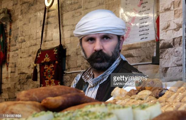 A Syrian Kurdish man sells sweets at a shop in Arbil the capital of the autonomous Kurdish region of northern Iraq on December 21 2019 Since conflict...