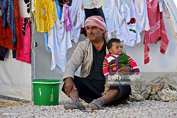 Syrian Kurdish man with a baby fled with a group from clashes between the Islamic State of Iraq and Levant militants and armed Syrian Kurdish forces...