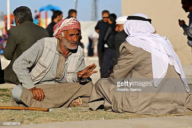 Syrian Kurdish old men, fled with a group from clashes between the Islamic State of Iraq and Levant militants and armed Syrian Kurdish forces, sit...