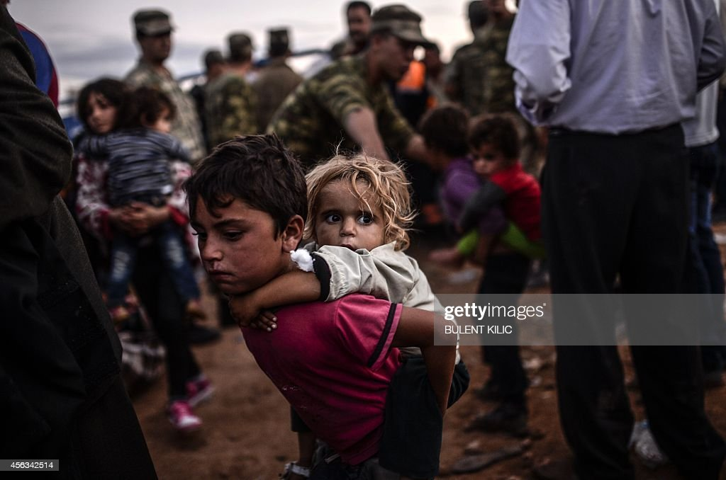 Syrian Kurdish people arrive at the border between Syria and Turkey after several mortars hit both side in the southeastern town of Suruc, in the Sanliurfa province on September 29, 2014. Tens of thousands of Syrian Kurds flooded into Turkey fleeing an onslaught by the Islamic State (IS) group that prompted an appeal for international intervention. Some of the refugee now want to return to protect their homes and join the fight against IS militants.