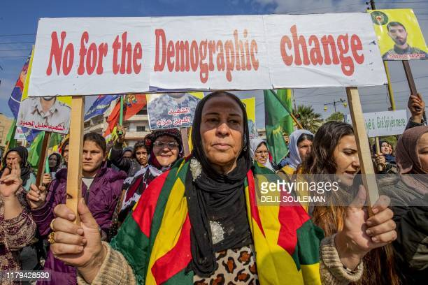 A Syrian Kurdish protester holds a sign during a demonstration against Turkish threats in the northeastern city of Qamishli the defacto capital of...