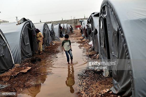 A Syrian Kurdish refugees boy walks in a water on October 11 2014 in a camp in the town of Suruc in Sanliurfa province About 300000 Syrian Kurd...