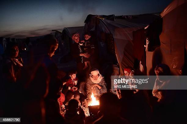 Syrian Kurdish refugees gather around fire in a refugee camp in Suruc Sanliurfa province on November 11 2014 AFP PHOTO / ARIS MESSINIS