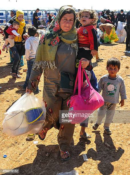 Syrian Kurdish refugees walk with their belongings after crossing into Turkey near the southeastern Turkish town of Suruc in Sanliurfa province...