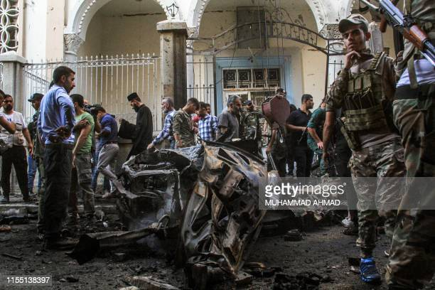Syrian Kurdish security forces inspect the wreckage of a rigged car which detonated outside the Syriac Orthodox Church of the Virgin Mary in the...