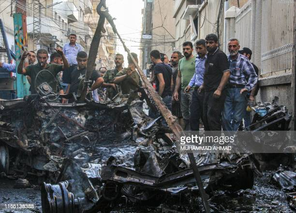Syrian Kurdish security forces lift the wreckage of a rigged car which detonated outside the Syriac Orthodox Church of the Virgin Mary in the...